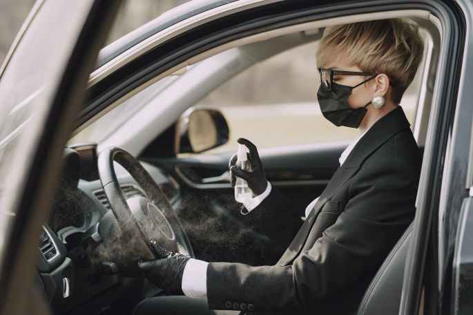 woman in formal clothes disinfecting steering wheel of car